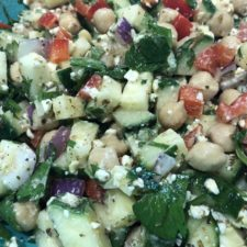 Close up of chickpeas, feta, chopped onions, red pepper and cucumber