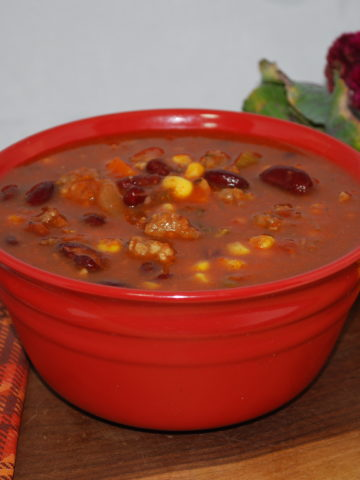 Italian Vegetable Soup in a red bowl with spoon, napkin and sunflowers behind it