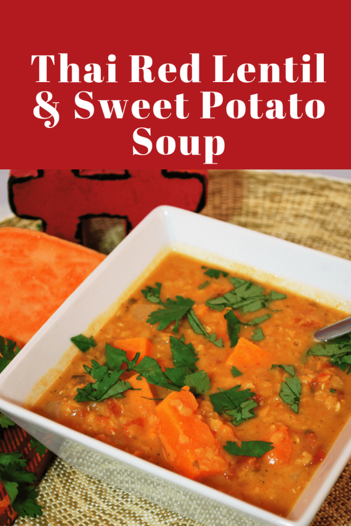 Thai red lentil & sweet potato soup in a white serving bowl, topped with chopped cilantro.