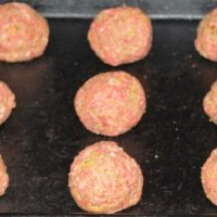 Baking sheet with 15 meatballs ready to bake
