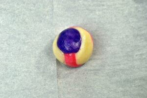 Ball of cookie dough with white, purple and pink coloured dough.