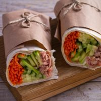 Tuna wraps on wooden background. horizontal