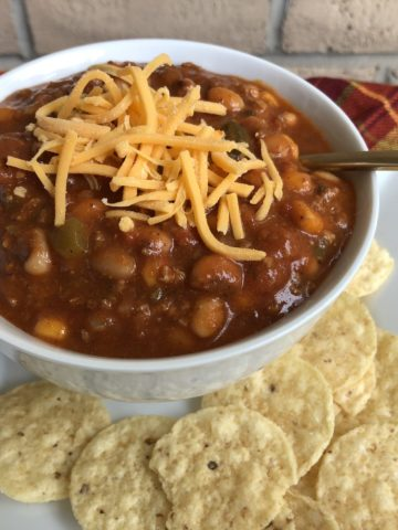 Taco Soup in a white bowl with shredded cheddar on top and tortilla chips on the side.