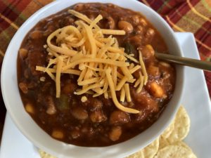 Close up of Taco Soup with shredded cheese on top.
