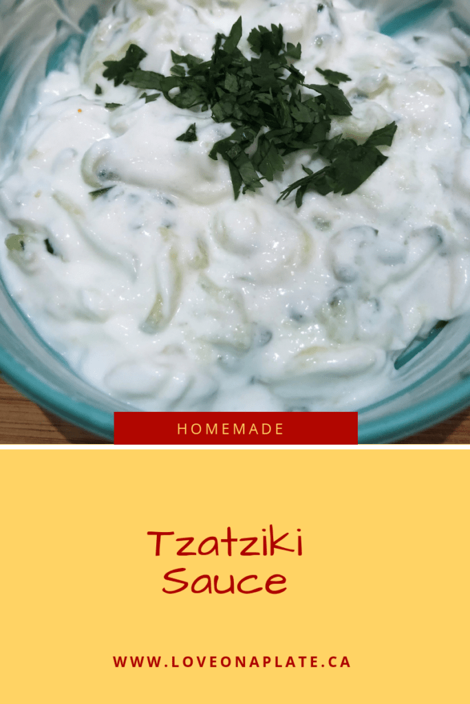 Tzatziki sauce topped with chopped mint in a bowl