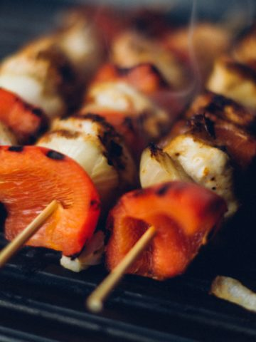 Pork Souvlaki with onions and red peppers on a grill