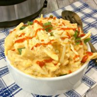 Cooked pasta with buffalo chicken cheese sauce in a white bowl