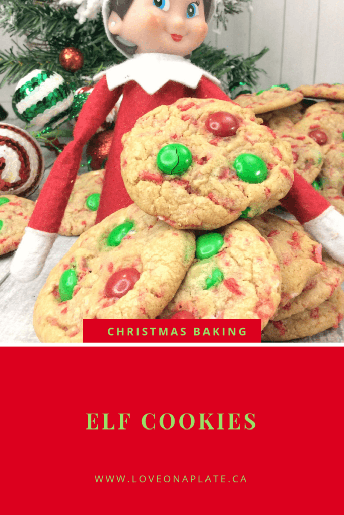Sugar cookies with red and green m&m's with an elf of a shelf holding them