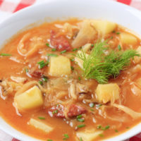 Cabbage and Kielbasa Soup in a white bowl.