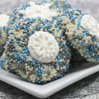 round sugar cookies with winter coloured sparkling sprinkles and an icing snowflake center.