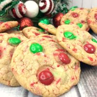 Cookies with red and green m&m's on a white plate on a wooden table.