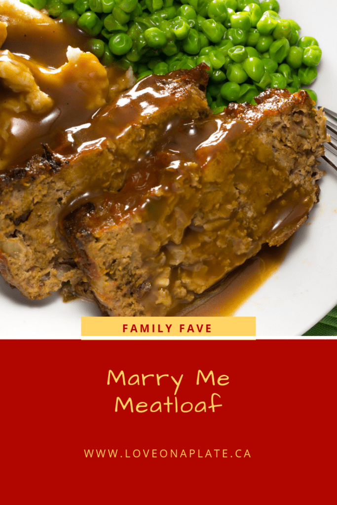Sliced meatloaf with gravy, mashed potatoes and peas on a white plate.