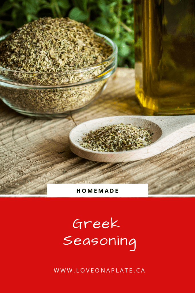 Homemade Greek Seasoning in a large glass bow, and a small wooden spoon with seasoning on it.