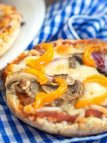 English Muffin with pizza sauce, melted cheese, sliced mushrooms and yellow peppers, and a blue checked napkin