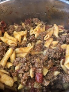 Cooked penne pasta and ground beef with a salsa tomato sauce in an instant pot