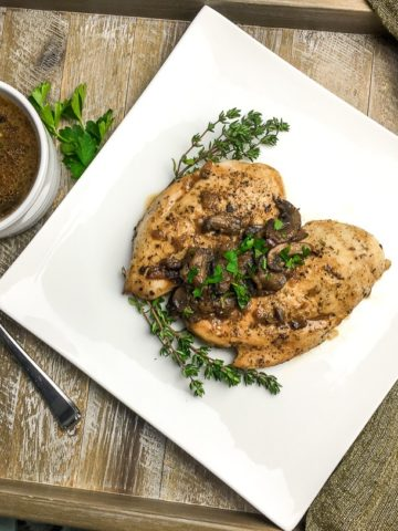 Seared chicken breasts with mushroom, onion, goat cheese sauce and a sprinkle of chopped parsley on a square white plate.