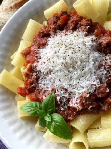 Three Meat Pasta Sauce served over rigatoni in a white bowl