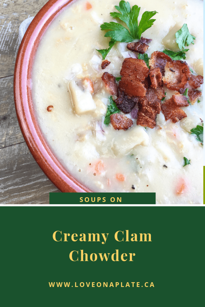 White creamy clam chowder topped with bacon and parsley in a soup bowl