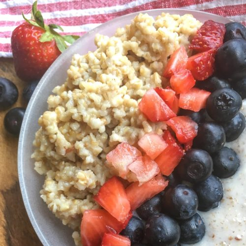 Cooked steel cut oats with yogurt, cut strawberries and blueberries