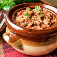 Stuffed Pepper soup with brown rice and tomatoes topped with parsley in a brown ceramic bowl