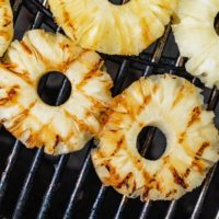 Three pieces of pineapple slices with grill marks on a bbq grill