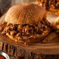 Hamburger bun filled with cooked ground beef in a sweet and smoky BBQ sauce