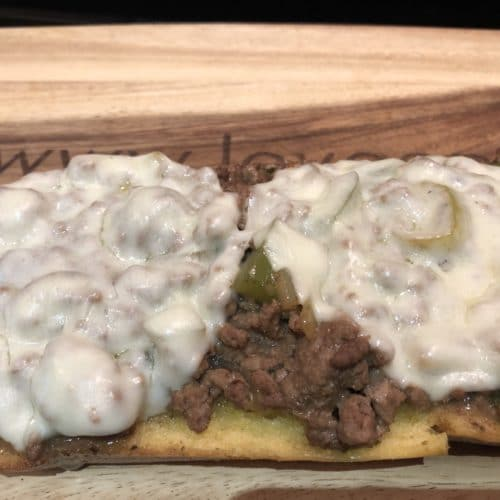 Wooden cutting board with Ground Beef and Gravy smothered in cheese