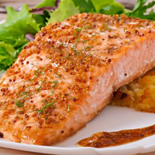 Salmon Fillet glazed with maple dijon sauce on a white plate with greens