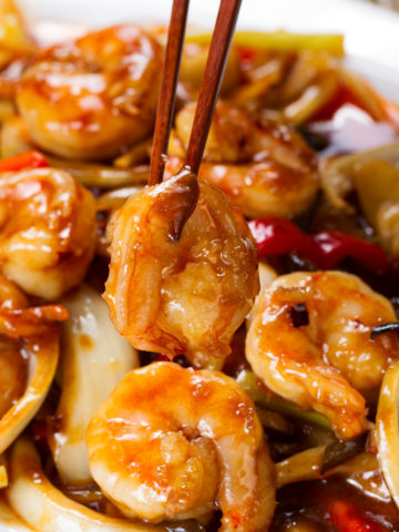 Shrimp, onions, peppers, dried chilies plated with chopsticks standing up