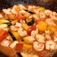 Homemade sweet and sour shrimp with red bell peppers, zucchini, onions simmering in sauce in a pan