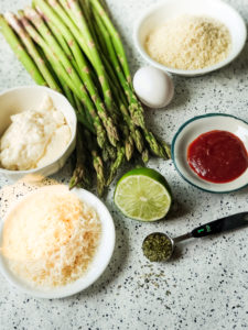 Fresh asparagus laying on a marble counter. Parmesan cheese grated, mayonnaise, Panko and Chipotle sauce are all shown in white bowls