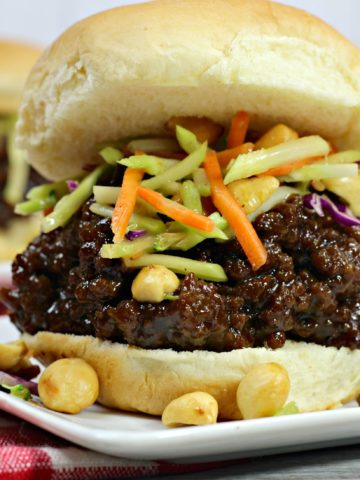 Thai seasoned ground beef on a toasted hamburger bun topped with broccoli slaw, on a white plate with peanuts scattered on it.