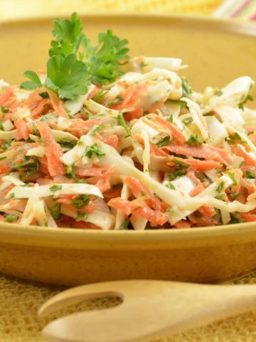 Shredded green and purple cabbage, carrots, with pineapple and cilantro in a large serving bowl with a wooden serving spoon.