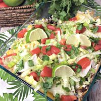 Glass Casserole dish topped with chopped lettuce, tomato, green onions and cilantro. Filling is ground turkey, black beans and corn.