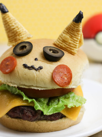 A Cheese burger on a bun decorated to look like Pikachu. 2 bugles are his ears, 2 slices of black olives are his eyes, two thin slices of pepperoni are his cheeks.