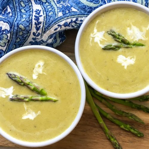 Two bowls of creamy Asparagus Soup, topped with asparagus tips and dollops of sour cream.