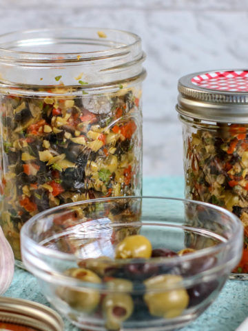 Chopped black, kalamata and green olives in a garlic parsley dressing, stored in small glass mason jars.