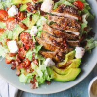 Sliced grilled chicken, slices of avocado, cherry tomatoes halved, bocconcini pearls, parmesan cheese and bacon on a bed of lettuce.