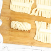 Wrapping the cheese sticks in crescent dough to form mummys