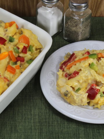 A white plate filled with Cheesy Chicken Noodle casserole, part of a white baking dish with the pasta in it.