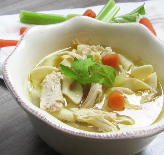 Chicken Broth, shredded cooked chicken, carrots and slices of celery in a white bowl with celery and carrots on the table.