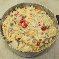 Cooked noodles with red, green, and orange peppers, cheese and chicken