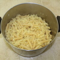 Cooked noodles in a stainless steel pot