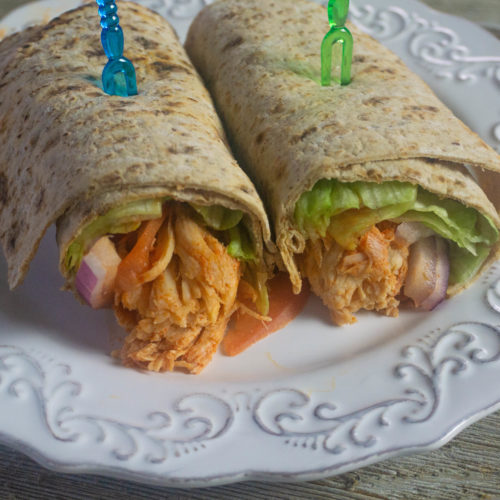 Buffalo Chicken filling in a wrap with lettuce, tomatoes, red onions. Wrap is cut in half and filling is showing.