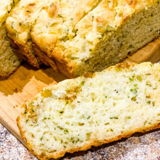 Garlic Cheese Quick bread on a wooden cutting board sliced.