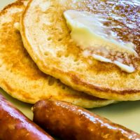Two golden brown pancakes with butter and syrup on top, 3 golden browned breadfast sausage