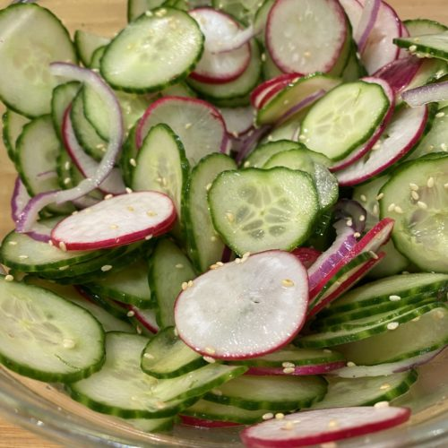 Thinkly sliced cucumbers, radish, red onion in a large glass mixing bowl. topped with toasted sesame seeds