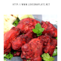 pieces of Tandoori chicken on a slate platter with pieces of naan cut into quarter
