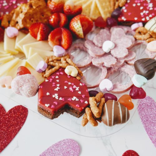 Valentines Charcuterie board; sliced deli meat in heart shapes, cheddar cheese, crackers, brownies, chocolate hears, gummy hearts, strawberries, cherries, mandarin oranges.